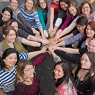 Women of certain affinity putting their hands together for a group huddle