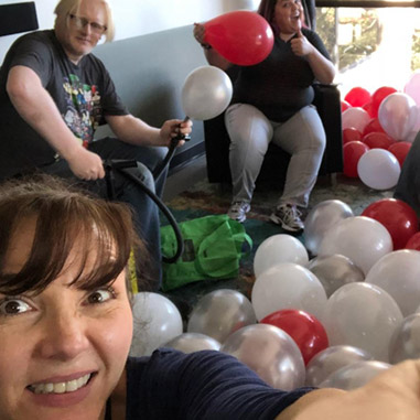 Certain Affinity employees blowing up dozens of red, white, and silver balloons