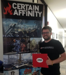 Tyler Wolverton with his award in front of Certain Affinity banner
